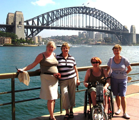 Four tourists, one in a wheelchair and three standing, at the Sydney Opera House with the Sydney Harbour Bridge in the background.